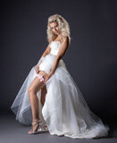Image of sensual young bride shows garter on leg. Close-up Stock Photo