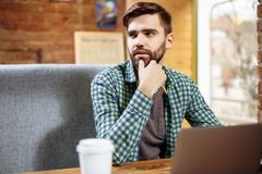 Image of serious bearded young man sitting in cafe while using laptop. Stock Photos