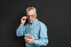 Image of serious mature elderly man 60s with gray hair looking o. N cell phone with pensive look while reading or scrolling news feed isolated over black Stock Photo