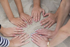 Image of several hands on sand in the form of circle Royalty Free Stock Photos