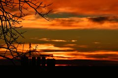 Grain Storage Silos. An image of several tall grain storage silos during a fiery red sunset royalty free stock photography