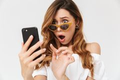 Image of shocked brunette woman 20s looking at smartphone from u. Nder sunglasses with open mouth isolated over white background stock photos