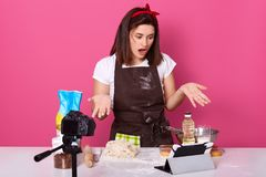 Image of shocked impressed female raising her hands, opening mouth widely, looking at tablet, being confused with recipe, making. Dough, wearing dirty brown royalty free stock photography