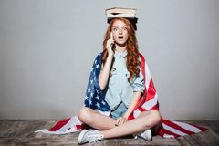 Shocked redhead young lady talking by phone. Image of shocked redhead young lady holding book on head wearing USA flag. Looking camera talking by phone Stock Photography