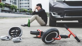 Image of shocked and scared driver after accident involved Kid`s bike and helmet lying on the road on pedestrian crossing after. Accident collision with drunk royalty free stock images