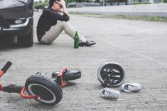 Image of shocked and scared driver after accident involved Kid`s bike and helmet lying on the road on pedestrian crossing after. Accident collision with drunk stock photography