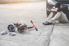Image of shocked and scared driver after accident involved Kid`s bike and helmet lying on the road on pedestrian crossing after. Accident collision with drunk royalty free stock photography