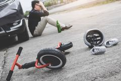 Image of shocked and scared driver after accident involved Kid`s bike and helmet lying on the road on pedestrian crossing after. Accident collision with drunk royalty free stock photo