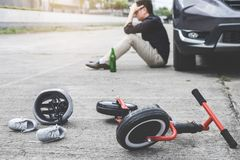 Image of shocked and scared driver after accident involved Kid`s bike and helmet lying on the road on pedestrian crossing after. Accident collision with drunk royalty free stock photos
