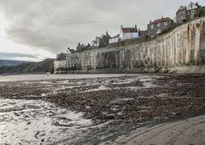 Robin Hood`s Bay, the beach and the houses. This image shows a beach and some houses in Robin Hood`s Bay, Yorkshire on a sunny day in December Stock Photo