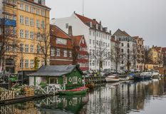 A canal and some colorful buildings in Copenhagen, Denmark. This image shows a canal, Copenhagen, Denmark. It was taken on a cloudy day in November 2017 Royalty Free Stock Images