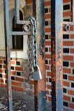 Padlock with chain on the open gate. This image shows a closeup of a metal door open with a chain and a new padlock Royalty Free Stock Photos