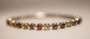 Colorful Amber bracelet, a closeup. Royalty Free Stock Images