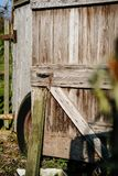 Dilapidated old wooden shed used by a rural tramp, seen with the door opened. The image shows the door wedged open and an old tyre at the back prevents the door Royalty Free Stock Images