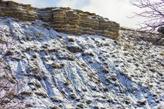 Layers of Winter. Image shows a ledge of limestone and shale. As the snow settles going downhill or down the slope. Liked how the light hit all the layers of stock photography