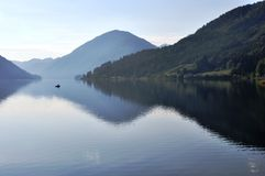 Lake Weissensee, Austria. Image shows panoramic view to lake Weissensee with fisherman and boat, Austria, Techendorf, Carinthia Royalty Free Stock Image