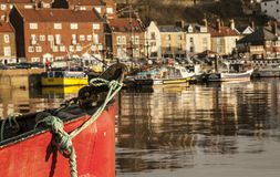 Whitby, Yorkshire, England - the boats. This image shows some houses in Whitby, Yorkshire. It was taken at sunset, we can see the reflection of the houses in Royalty Free Stock Image