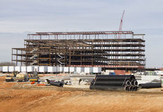 Hospital Construction Site. This image shows the steel framework of a large building under construction.  The job site includes building materials, a large crane Royalty Free Stock Image