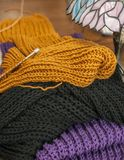 Colorful scarves, lines of the pattern - work in progress. This image shows three colorful scarves, mustard, black and a violet one, one of them is still being Stock Image