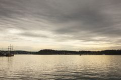 Fjord at sunset - Oslo, Norway; moody and gloomy. This image shows a view of a fjord in Oslo, Norway. It was taken at sunset on a cloudy day in autumn 2017 stock photo