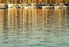 Oslo - fjord, boats and blue waves at golden sunset. This image shows a view of Oslo - some boats floating on the golden waters of the fjord at sunset; shiny Stock Images