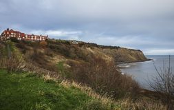 Robin Hood`s Bay - the shore and the houses. The image shows a view of Robin Hood`s Bay - a village in Yorkshire. We can see some meadows and houses on the royalty free stock image
