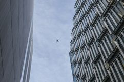 City of London, modern buildings and a plane. This image shows a view of some of the modern building in London, looking up. There`s a plane visible in the sky Stock Photo