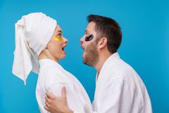 Image on side of man and woman with gel pads under eyes and in white robe. Image on side of men and women with gel pads under eyes and in white robe on empty stock photography