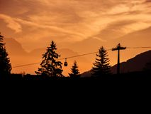 Image of silhouettes of ski lift and trees during sunrise in the early morning stock images