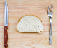The image of the slice of bread on a wooden table with fork and knife Stock Images