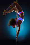 Image of slim girl dancing on pole under UV light Royalty Free Stock Images