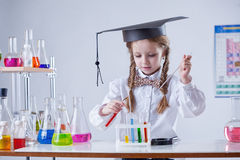 Image of smart girl mixing tubes in laboratory Royalty Free Stock Photos