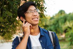 Image of Smiling asian male student in eyeglasses listening music royalty free stock photography