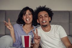 Image of smiling couple sitting on floor near sofa at home and looking aside while eating popcorn royalty free stock photo