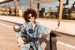 Image of smiling curly woman in sunglasses sitting on motorbike Royalty Free Stock Image