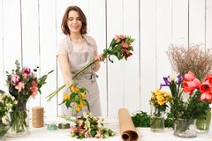 Pretty smiling florist woman with different flowers. Image of smiling florist woman standing near table with different flowers and looking aside in workshop Royalty Free Stock Photo