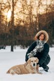 Image of smiling girl on walk with dog on background of trees. In winter park at afternoon Royalty Free Stock Photography