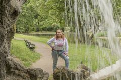 Image of a smiling woman next to a small waterfall in the Citadel park in Ghent Belgium. On a beautiful day, copy space, travel, adventure concept royalty free stock photo