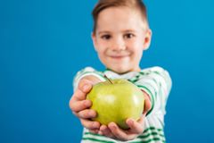 Image of Smiling young boy giving apple at the camera. Over blue background Royalty Free Stock Images