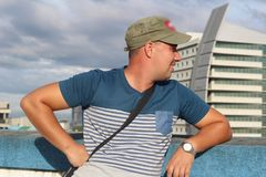 A young man in a cap in profile against the background of buildings royalty free stock photo