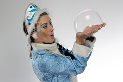 Image of snow maiden and soap bubble in her hands Royalty Free Stock Images