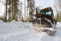 Image of snowblower clears road in forest Stock Photos