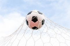Soccer football in Goal net with the sky field. Royalty Free Stock Photos