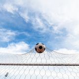 Soccer football in Goal net with the sky field. Royalty Free Stock Photography