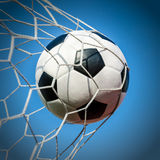 Soccer football in Goal net with the sky field. Royalty Free Stock Image