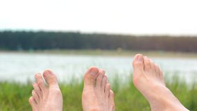 Image of soles of two people lying on beach. Summer holidays concept. Travel. Tourism. Vacation. Landscape. Legs. Children. Blur Background stock footage