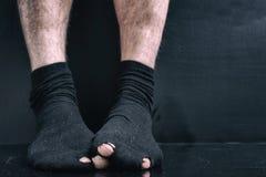 Image sous le film, jambes dans des chaussettes de trous noirs le concept de la pauvreté, faillite, pauvres, dette photos stock