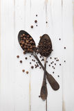 Image of spoons full of black peppercorn and allspice on board Royalty Free Stock Photo