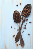 Image of spoons full of black peppercorn and allspice on board Royalty Free Stock Image