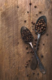 Image of spoons full of black peppercorn and allspice on board Stock Photos